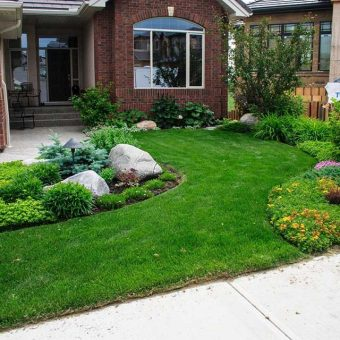 A small front yard or landscape with Kentucky Bluegrass lawn. Aggregate driveway and landscaping rocks.