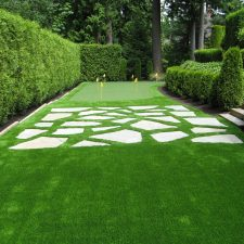 Artificial grass with stepping stones and synthetic lawn. Large green trees and sloped backyard