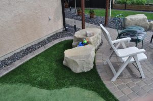 Big landscaping rocks on artificial grass and concrete patio and curb appeal. Concrete walkway & lawn chairs