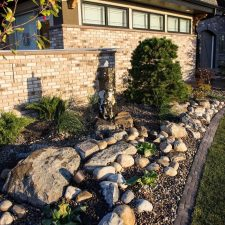 Brick shaped retaining wall matching house. Brown curb appeal