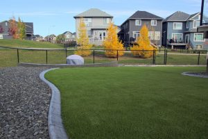 Calgary landscape with concrete curbing and artificial grass. Gravel on the left and small retaining wall.