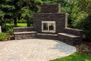 Calgary landscape with custom fireplace with retaining wall and concrete patio