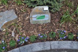 Concrete curbing stone showcasing curb design logo. concrete curb appeal with small purple flowers and mulch