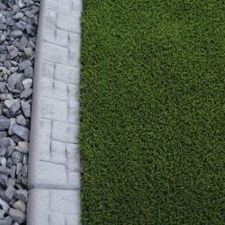 Curb Appeal used to separate synthetic lawn and gravel. Lush dark green artificial grass colors.