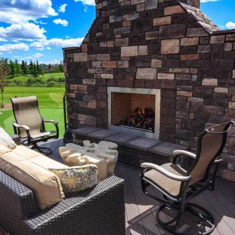 Custom built fireplace with dark shaded rock and stone. Unique Outdoor furniture. Glass railing and artificial grass.