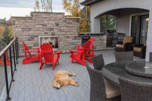 Custom deck with beautiful fireplace and outdoor kitchen. Dog sleeping on the deck.
