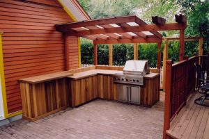 Entry level outdoor kitchen with pergola. Dark cedar wood and stone patio.