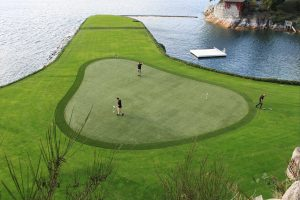 Drone footage of a golf course 18th hole with artificial grass backing on a lake.