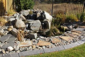 Irrigation installation and water fall with pond. Concrete curbing separating gravel with green lawn.