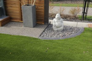 Landscape with large Buddha statue nest to artificial grass. Cedar privacy wall and aggregate concrete.