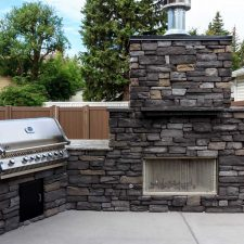 Large outdoor fireplace and outdoor kitchen with riverstone and granite counter-tops.