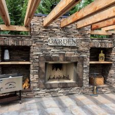 Large outdoor fireplace with cedar wood pergola. Concrete patio next to the large fireplace.