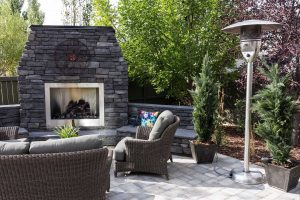 Side view of a Custom large landscape in Calgary with Fireplace. Concrete patio with hybrid fireplace and outdoor kitchen. High end outdoor furniture.