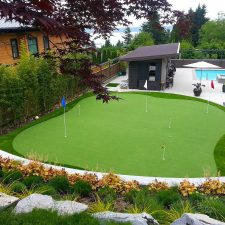 Large putting green landscape made of synthetic lawn or artificial grass. Swimming pool and concrete patio.