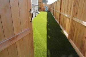 light cedar fence and artificial grass and playpen for kids. Un-stained fence side view.