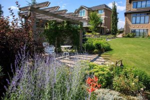 Marvelous calgary landscape with flower beds and large lawn.