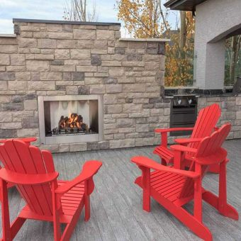 Outdoor Kitchen and fireplace with a custom built deck. Glass railing on sides of deck. Bright red outdoor furniture.