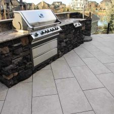 Breath taking outdoor kitchen in Calgary. Large tiles and custom granite counter-tops with BBQ.