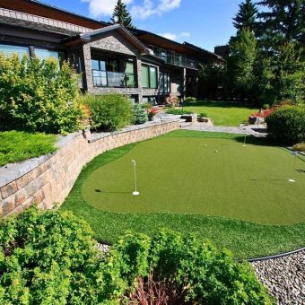 Outdoor Landscape with retaining walls, trees, shrubs and artificial grass putting green.