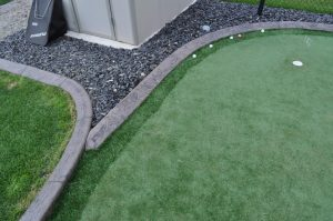 Putting green landscape and concrete curbing. Golf balls on putting green made of synthetic grass.