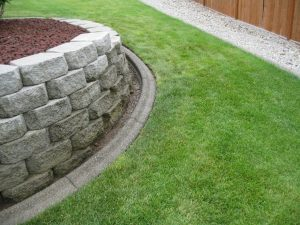 Retaining wall surrounded with concrete curbing & green grass. Dark cedar fence and gravel.