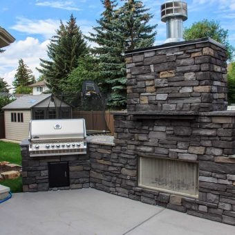Side view of a wood burning fireplace with BBQ built into the outdoor kitchen. Concrete patio and granite counter-tops