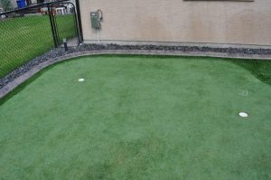 Small Calgary backyard putting green with curb appeal. Golf turf with golf holes.