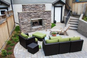 Small Calgary backyard with fireplace and concrete patio. Large outdoor furniture and aggregate concrete steps.