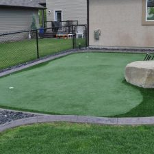 Small Calgary landscape with curb appeal and artificial grass. Made for putting green. Golf balls on turf. Large landscaping rocks.