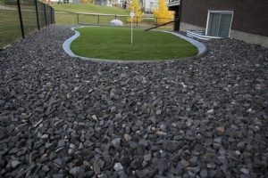 Small putting green with synthetic lawn or artificial grass. Concrete curbing separating artificial grass with gravel. Backed on a Calgary green space.