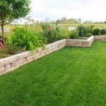 Modern and small retaining wall separating flower beds to green lawn