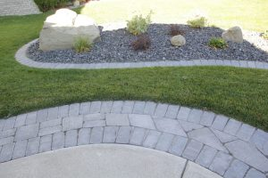 Stone walkway with green lawn and concrete curbing. Large & small landscaping rocks with concrete patio.