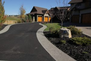Stunning asphalt driveway to large Calgary home. Large landscaping rock with trees and green lawn.