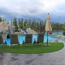 Stunning swimming pool surrounded with artificial grass or synthetic lawn.