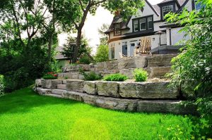 Unique retaining wall with natural rocks. Sloped backyard landscape. Green luscious lawn in the front.