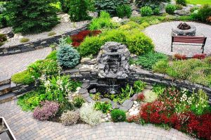 Unique water fountain and fire-pit surrounded with custom walkways. Beautiful flower beds.