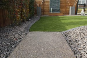 Walkway made of aggregate concrete and artificial grass. Concrete curbing and cedar wood privacy wall