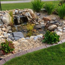 Waterfall with large rocks and brown curb appeal