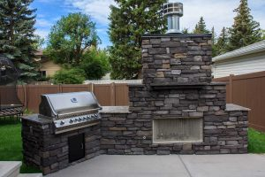 Wood burning fireplace with BBQ built into the outdoor kitchen. Concrete patio and granite counter-tops